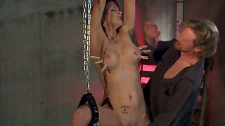 Sub is bound nigh chains while Master shoves toys in her cunt
